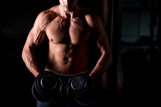 Homem musculoso fazendo exercícios com halteres no centro de fitness Foto gratuita