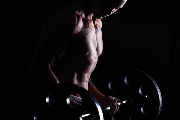 Homem musculoso fazendo levantamento de peso no centro de fitness Foto gratuita
