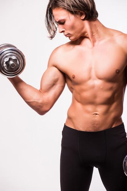 Homem musculoso fisiculturista fazendo exercícios com halteres isolados na parede branca Foto gratuita