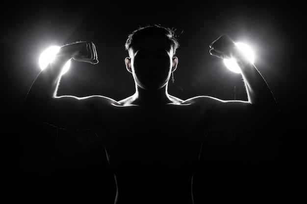 Homem musculoso fitness exercícios estilo de vida saudável em silhueta de fundo escuro luz de fundo Foto Premium