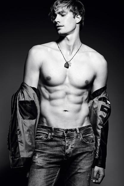 Homem musculoso jovem bonito modelo masculino apto posando no estúdio, mostrando seus músculos abdominais Foto gratuita