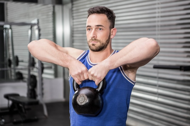 Homem musculoso, levantando o kettlebell pesado no ginásio crossfit Foto Premium