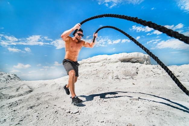 Homem musculoso malhando com cordas de batalha. atlético jovem malhando com cordas de batalha ao ar livre. exercício em forma de esporte. Foto Premium