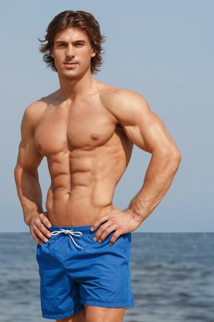 Homem musculoso na praia Foto Premium
