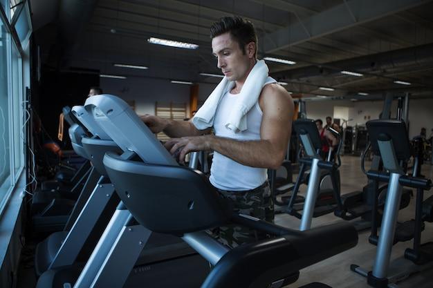 Homem musculoso usando máquina de exercício no ginásio Foto Premium