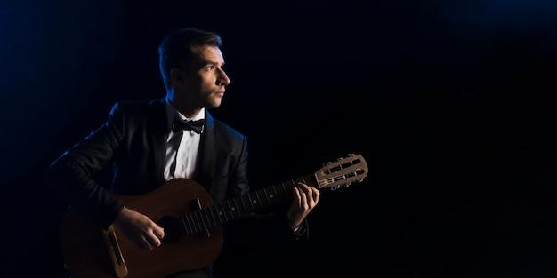 Homem músico com gravata borboleta tocando violão clássico Foto gratuita