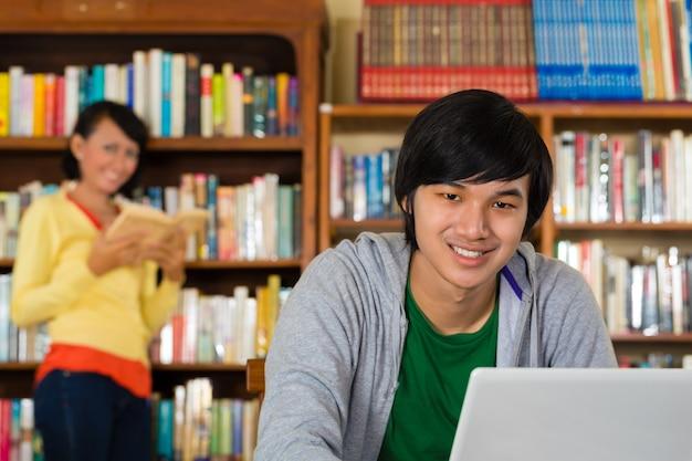 Homem na biblioteca com laptop Foto Premium