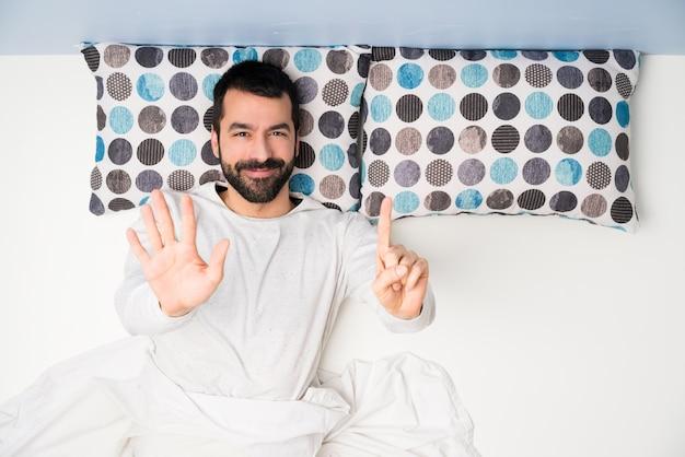 Homem na cama em vista superior, contando seis com os dedos Foto Premium