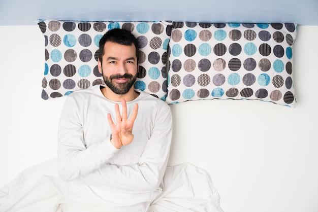 Homem na cama em vista superior feliz e contando quatro com os dedos Foto Premium