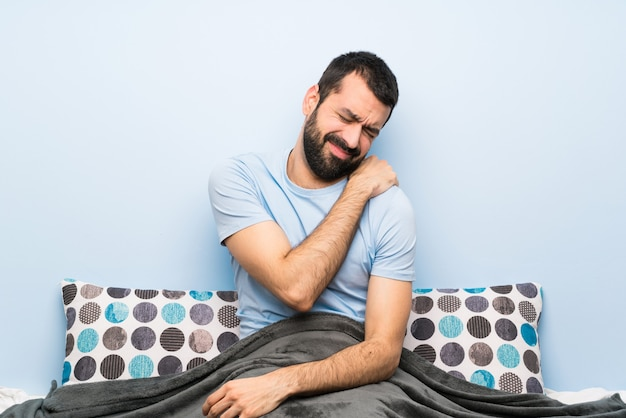 Homem na cama sofrendo de dor no ombro por ter feito um esforço Foto Premium