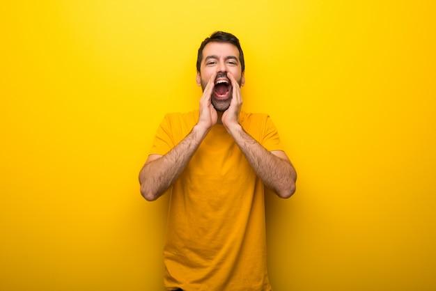 Homem na cor amarela vibrante isolada gritando e anunciando algo Foto Premium
