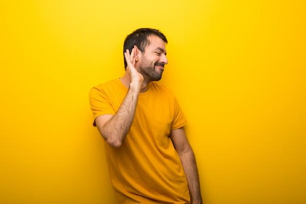 Homem na cor amarela vibrante isolada ouvindo algo, colocando a mão sobre a orelha Foto Premium