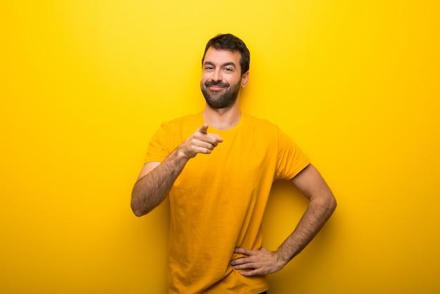 Homem na cor amarela vibrante isolado aponta o dedo para você com uma expressão confiante Foto Premium