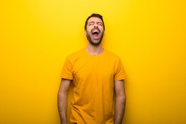 Homem na cor amarelo vibrante isolado gritando para a frente com a boca aberta Foto Premium
