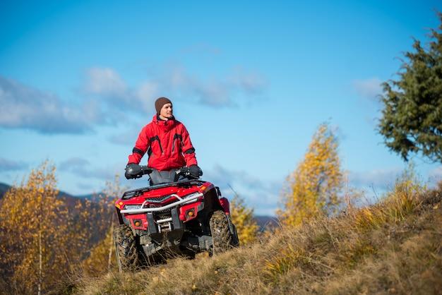Homem na moto quad atv vermelho contra o céu azul Foto Premium