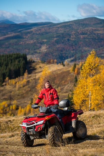 Homem na moto-quatro nas montanhas em um fundo desfocado montanhas poderosas Foto Premium