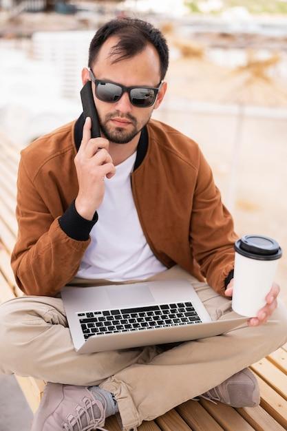 Homem na praia trabalhando no laptop enquanto tomando café Foto gratuita