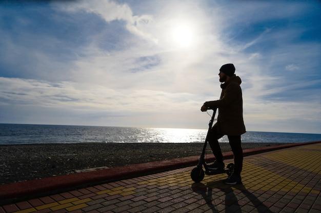 Homem na scooter ao pôr do sol, silhueta, espaço livre Foto Premium