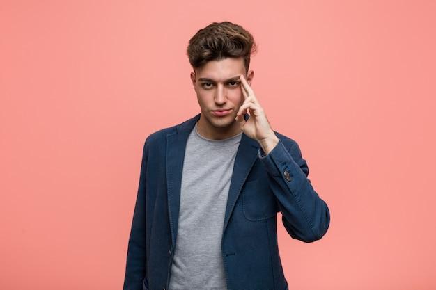 Homem natural do negócio novo que aponta o templo com o dedo, pensando, focalizado em uma tarefa. Foto Premium