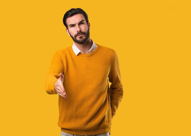 Homem natural novo que alcança para fora para cumprimentar alguém Foto Premium
