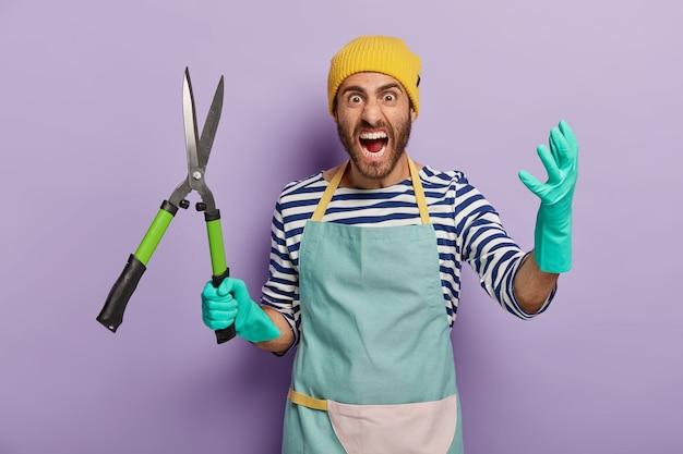Homem negativo indignado segura tesouras de poda ou tesouras de podar, grita de raiva, trabalha no jardim Foto gratuita