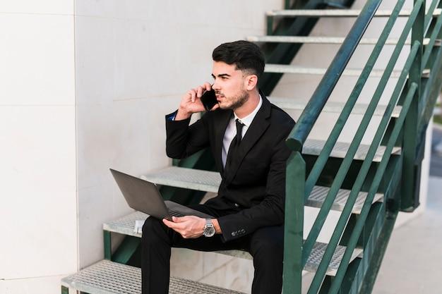 Homem negócio, com, laptop, e, telefone móvel Foto gratuita