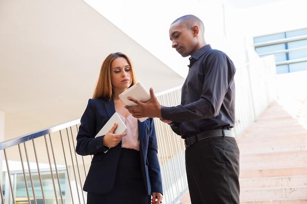 Homem negócio sério, mostrando, colega, tabuleta, tela, ligado, escadas Foto gratuita