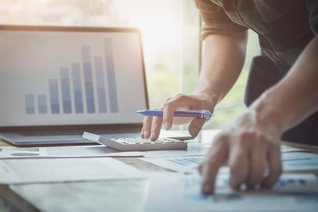 Homem negócio, usando, calculadora, revisar, balanço anual, usando, laptop, computador Foto Premium