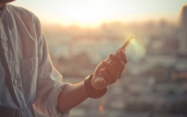 Homem negócio, usando, um, esperto, telefone, mãos, em, céu ocaso, ligado, obscurecido, cidade urbana, como, fundo Foto Premium