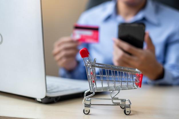 Homem negócios asiático, segurando, cartão crédito, usando, laptop, e, esperto, telefone Foto Premium