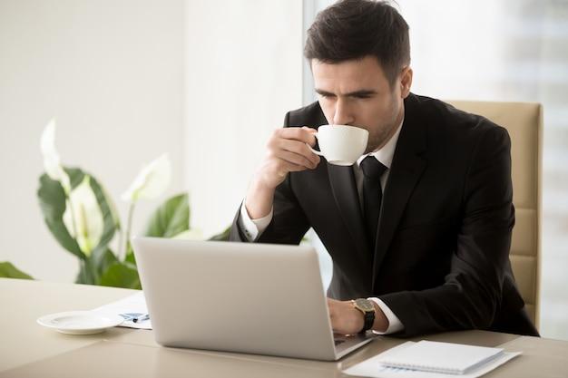 Homem negócios, café bebendo, quando, trabalhando, em, escritório Foto gratuita