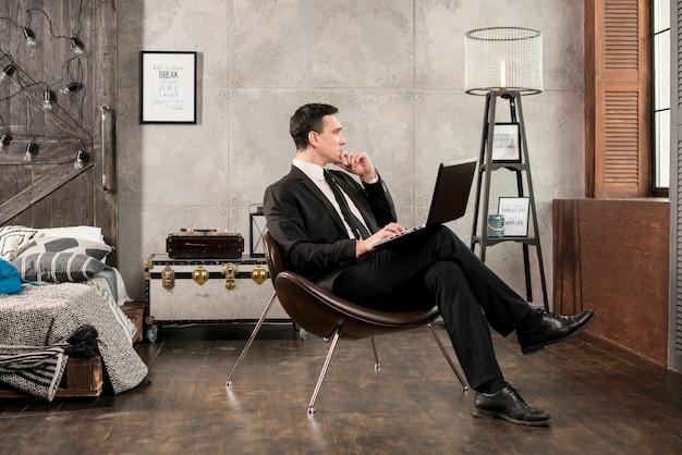 Homem negócios, com, laptop, olhando, e, pensando Foto gratuita