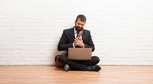 Homem negócios, com, seu, laptop, sentar chão, tendo, um, dor, coração Foto Premium