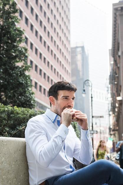 Homem negócios, comer, ligado, banco Foto gratuita