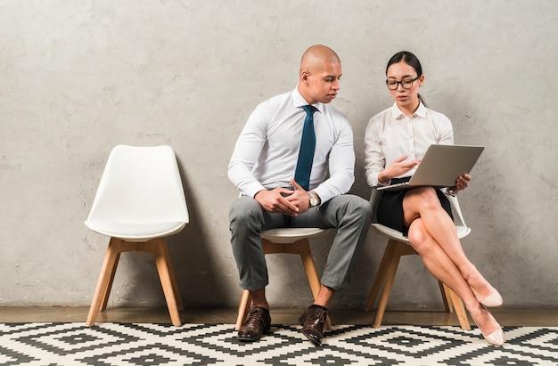 Homem negócios, e, executiva, sentando, ligado, cadeira, discutir, algo, usando computador portátil Foto gratuita