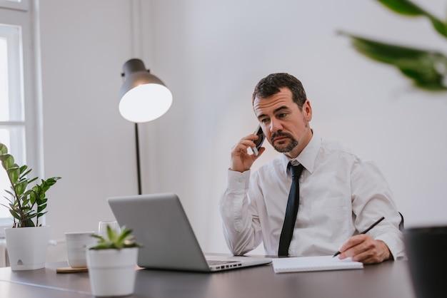 Homem negócios, em, escritório, falando telefone Foto Premium