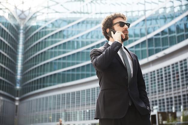 Homem negócios, falando, para, móvel, em, urbano, cidade Foto Premium
