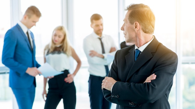 Homem negócios maduro, com, braços dobrados, olhar, seu, colegas, em, escritório Foto gratuita