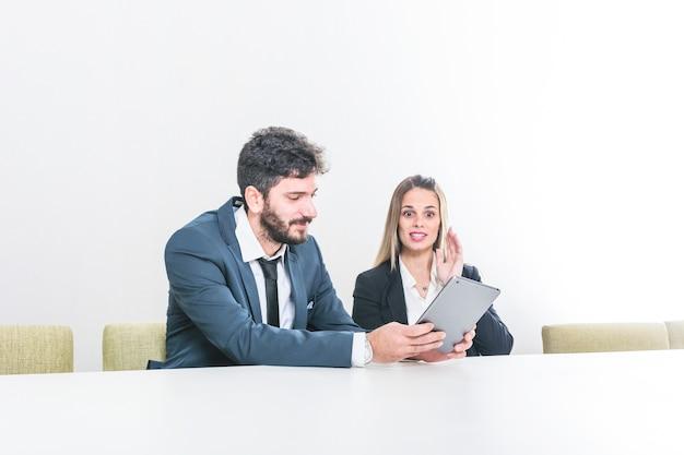 Homem negócios, mostrando, tablete digital, para, dela, colega, sentando, em, reunião diretoria Foto gratuita