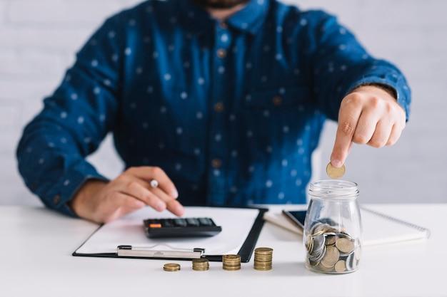 Homem negócios, pôr, moedas, em, jarro, usando, calculadora, em, local trabalho Foto gratuita