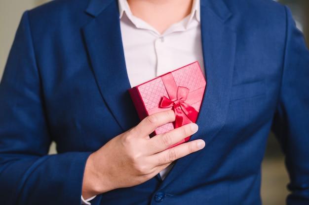 Homem negócios, segurando, a, vermelho, caixa presente Foto Premium