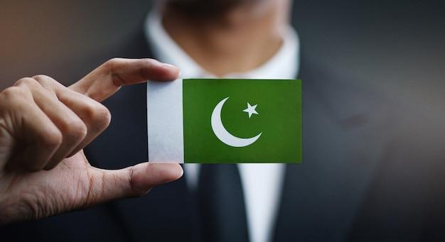 Homem negócios, segurando, cartão, bandeira paquistão Foto Premium