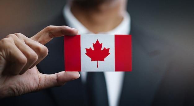 Homem negócios, segurando, cartão, de, bandeira canadá Foto Premium