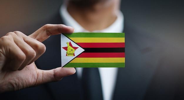 Homem negócios, segurando, cartão, de, zimbabwe, bandeira Foto Premium