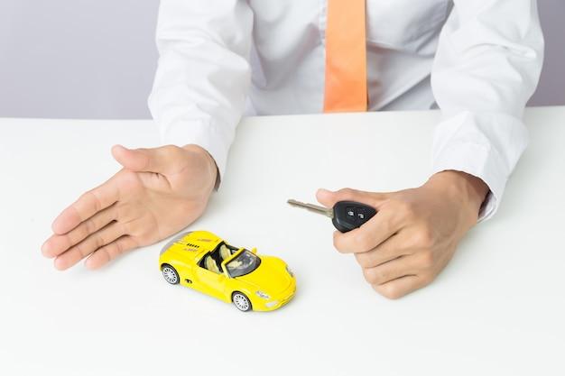 Homem negócios, segurando, um, carro, teclas, e, miniatura, car, modelo, auto negócio, e, financeiro, conceito Foto Premium