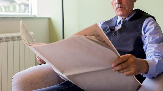 Homem negócios sênior, sentando, ligado, poltrona, jornal leitura Foto gratuita