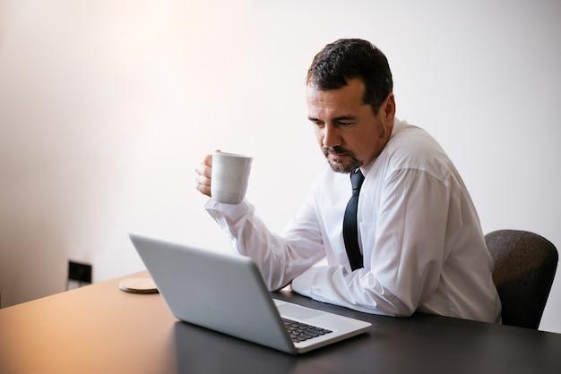 Homem negócios sênior, usando computador laptop, no trabalho Foto Premium