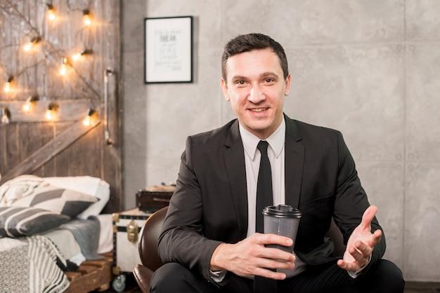 Homem negócios, sentando, com, xícara café, em, sala Foto gratuita
