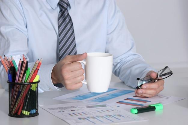 Homem negócios, sentando, em, escrivaninha escritório, tendo, um, café, partir Foto Premium