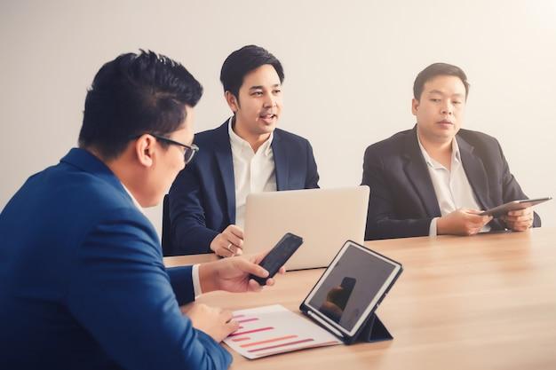 Homem negócios, serching, dados, com, smartphone, entre, reunião, incorporado, sucesso, brainstorming Foto Premium